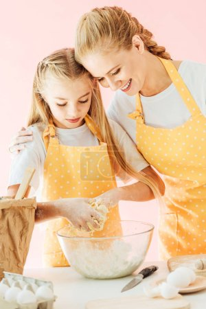 smiling mother and adorable little daughter in yellow aprons kneading dough together isolated on pink