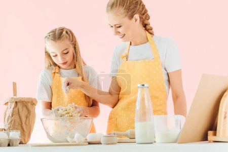 smiling mother and adorable little daughter in yellow aprons preparing dough together isolated on pink