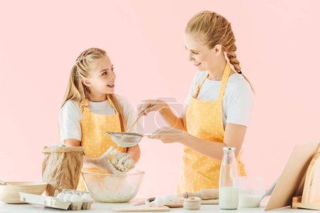 smiling mother and daughter in yellow aprons preparing dough together isolated on pink