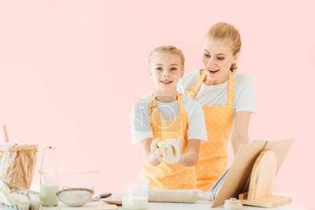 surprised young mother looking at daughter kneading dough isolated on pink