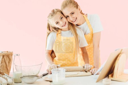 happy young mother and daughter kneading dough with rolling pin together and looking at camera isolated on pink