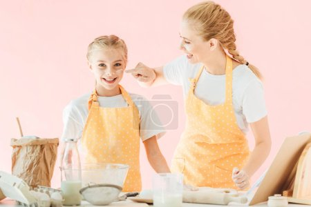 smiling mother and daughter with flour on faces cooking together isolated on pink