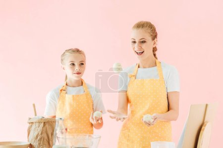 smiling mother and daughter juggling with dough pieces while cooking isolated on pink