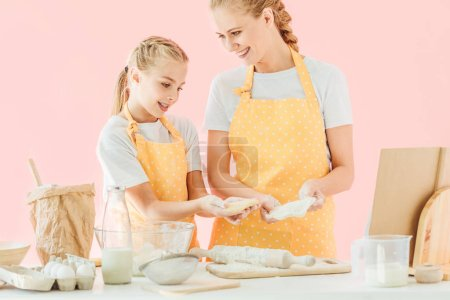 happy young mother and cute little daughter preparing dough together isolated on pink