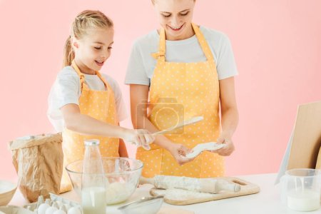 smiling young mother and cute little daughter preparing dough together isolated on pink