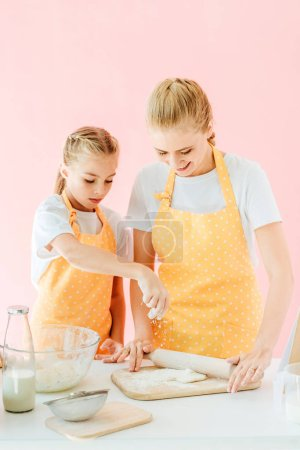 mother and adorable little daughter preparing dough together isolated on pink