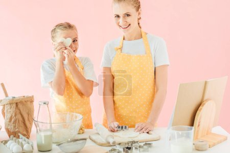 smiling young mother and daughter with dough in shape of heart looking at camera while preparing cookies isolated on pink