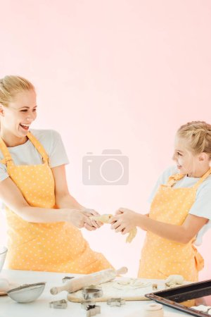 happy mother and daughter pulling piece of dough together and laughing isolated on pink