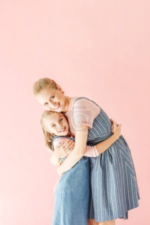 smiling young mother and daughter in blue dresses embracing and looking at camera isolated on pink