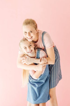Photo for Happy young mother and daughter in blue dresses embracing and looking at camera isolated on pink - Royalty Free Image