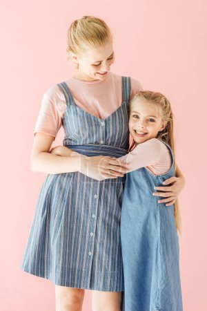 smiling mother and daughter in blue dresses embracing isolated on pink