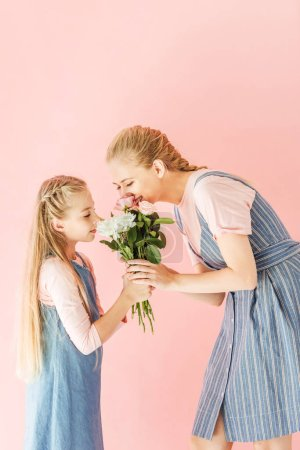 happy young mother and daughter sniffing bouquet together isolated on pink