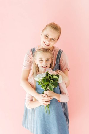 smiling young mother and daughter holding beautiful bouquet and looking at camera isolated on pink