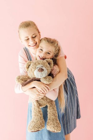 happy mother and daughter with teddy bear embracing isolated on pink