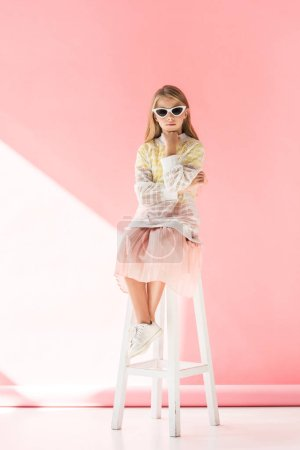 adorable pensive child in sunglasses sitting on stool on pink