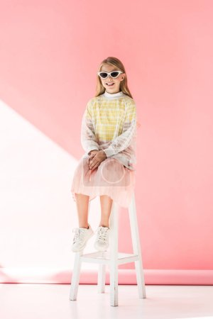 adorable stylish cheerful kid in sunglasses sitting on stool on pink