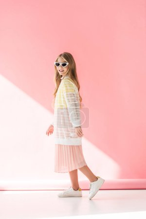 adorable stylish female youngster posing in elegant clothes and sunglasses on pink
