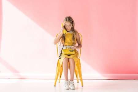 fashionable kid making call on retro phone while sitting on yellow chair on pink