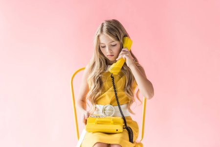 stylish blonde preteen child talking on retro telephone while sitting on yellow chair on pink