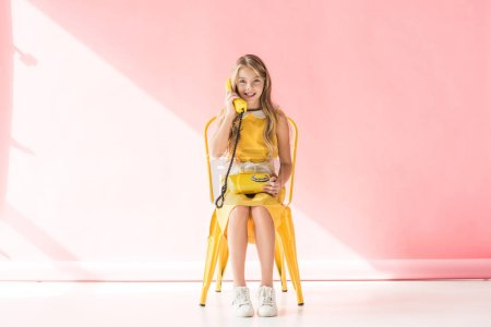 stylish smiling youngster talking on retro phone while sitting on yellow chair on pink