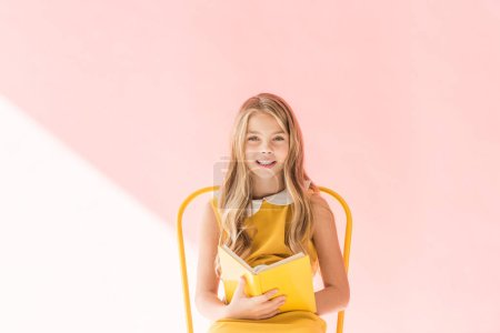 smiling kid reading book while sitting on yellow chair on pink