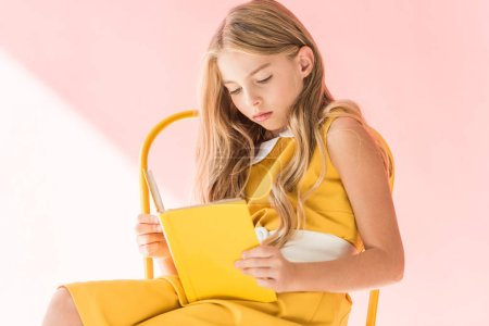 adorable elegant kid reading book while sitting on yellow chair on pink