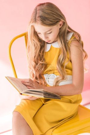 stylish blonde youngster reading book while sitting on yellow chair on pink