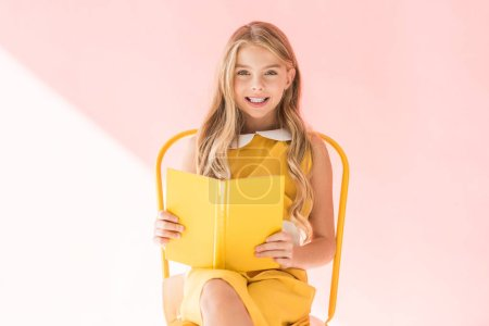 smiling fashionable kid reading book while sitting on yellow chair on pink