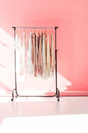 light stylish clothes on hangers in pink boutique
