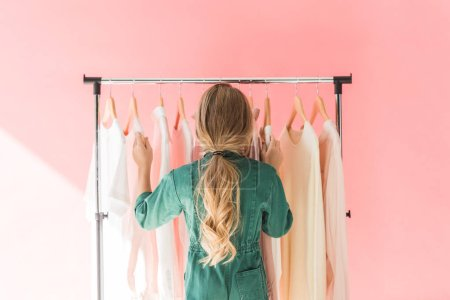 Photo for Rear view of blonde kid in trendy overalls choosing clothes on hangers - Royalty Free Image