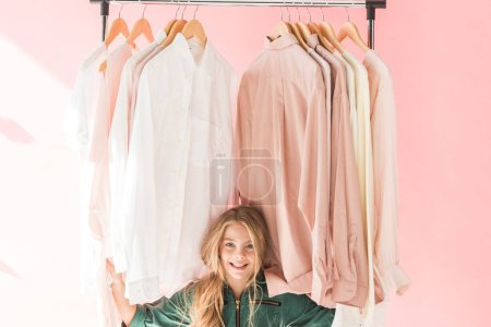 Photo for Cheerful charming kid in trendy overalls sitting under clothes on hangers - Royalty Free Image