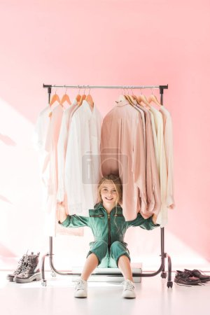 Photo for Stylish kid sitting under clothes on hangers in pink boutique - Royalty Free Image