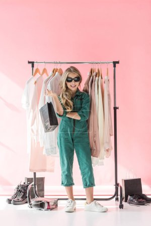 stylish child in overalls and sunglasses standing with shopping bag near clothes and footwear in boutique
