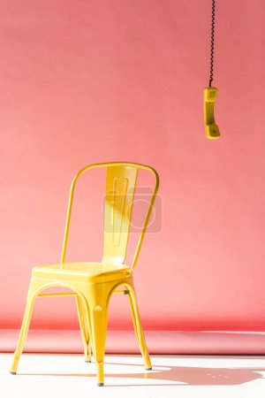 yellow chair and phone tube on pink