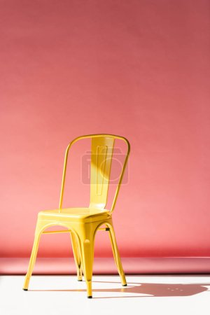 stylish yellow chair and on pink with copy space