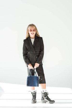 stylish smiling youngster in black suit and pink sunglasses posing with bag on grey