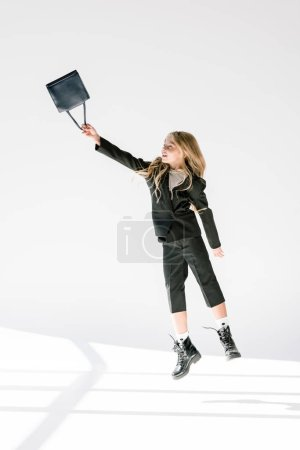 fashionable child in black suit flying with bag on grey