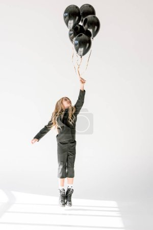 dreamy child jumping or flying with black balloons on grey