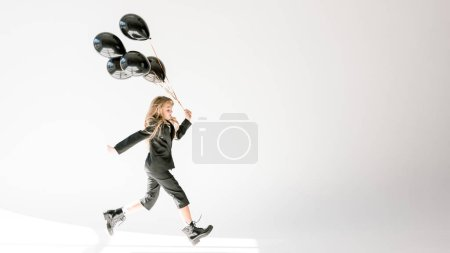 fashionable kid running with black balloons on grey