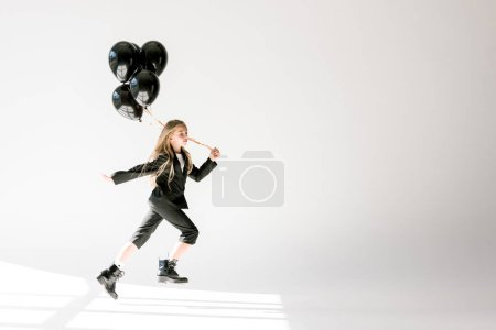 fashionable child in trendy suit jumping with black balloons on grey