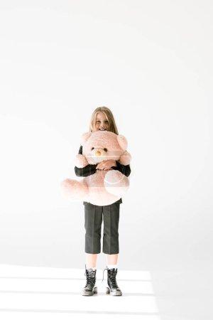 stylish cheerful kid in black suit holding big soft teddy bear on grey
