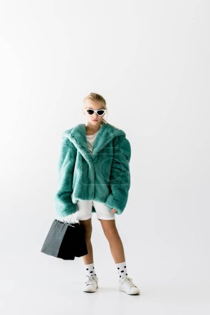 fashionable kid in turquoise fur coat posing with black shopping bags isolated on white