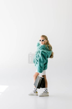 elegant child in turquoise fur coat and sunglasses posing with black shopping bags on white