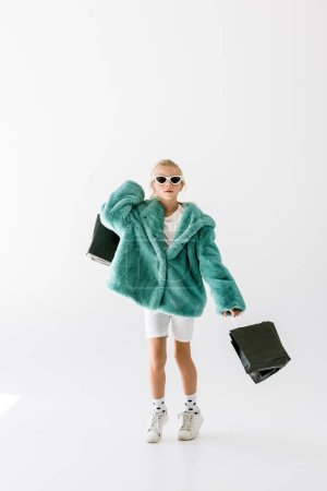 adorable stylish child in turquoise coat and sunglasses jumping with black shopping bags isolated on white