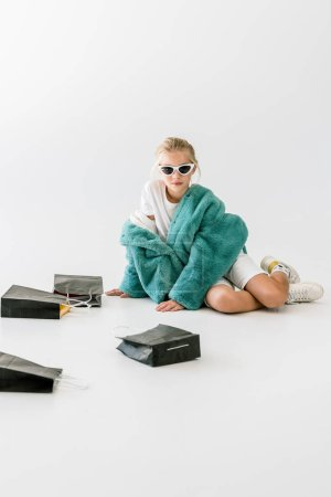 adorable fashionable child in turquoise fur coat sitting with black shopping bags on white