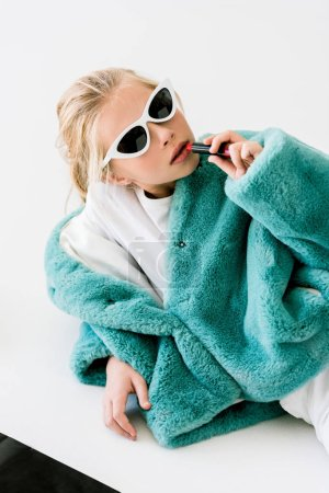 fashionable blonde child in turquoise fur coat and sunglasses applying lipstick on white