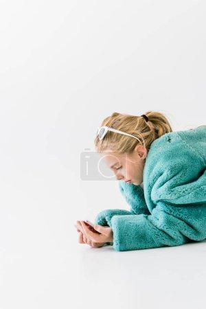 stylish kid in turquoise fur coat using smartphone isolated on white