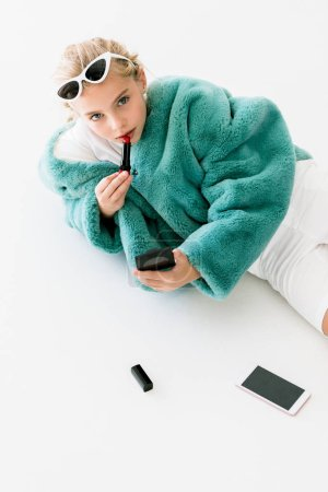 stylish blonde kid in turquoise fur coat applying lipstick with mirror while lying on white with smartphone
