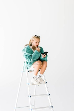 stylish kid in trendy fur coat applying lipstick and making makeup while sitting on ladder isolated on white
