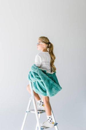 Photo pour Adorable gamin à la mode, qui pose en manteau de fourrure turquoise sur échelle isolée sur fond gris - image libre de droit